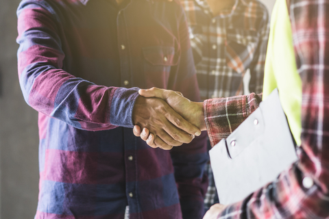 Two men wearing flannel shirts shake hands. The man in the foreground is wearing a yellow safety vest and holding a clipboard. He's a contractor looking to increase his customer base.