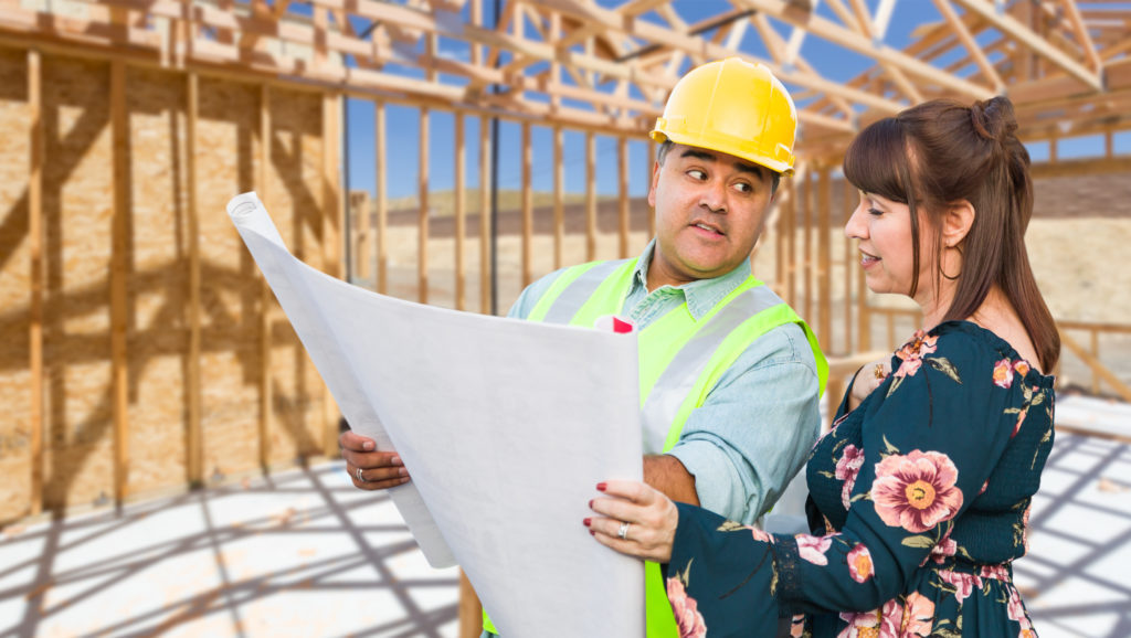 a contractor discusses plans with a satisfied customer