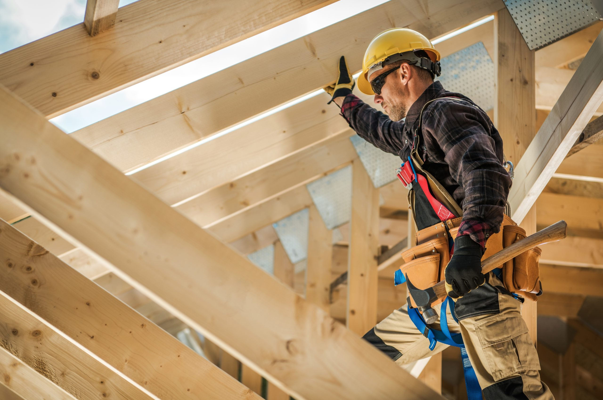 a contractor stands in the rafters of a building project