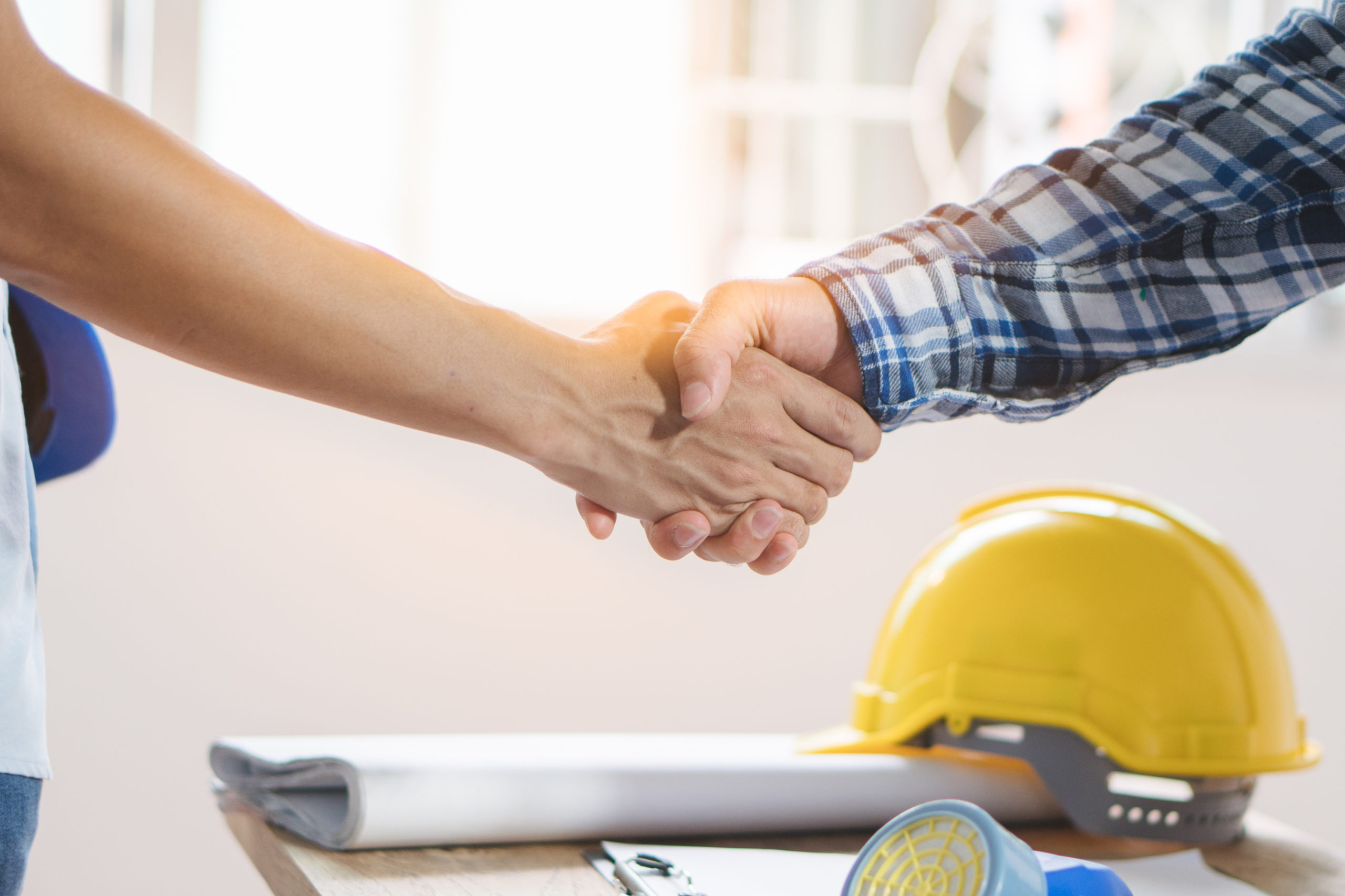 Two people shake hands as they agree to offer financing for home renovations and remodels. In the background is a contractor's hard hat and some folded blueprints.