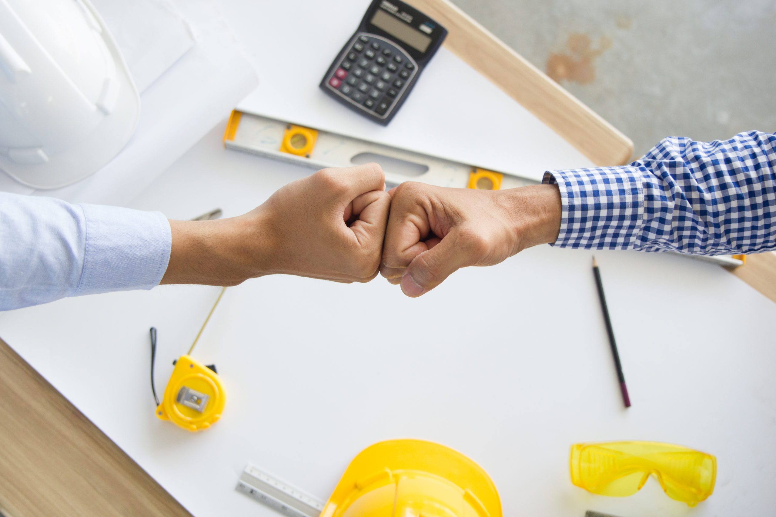 Two hands bump fists over a white table upon which are sitting a white hard hat, a level, a calculator, and a measuring tape. The contractor has closed the deal by offering contractor financing to his customer.
