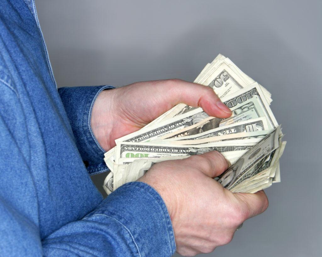 a business man in a blue shirt counts money