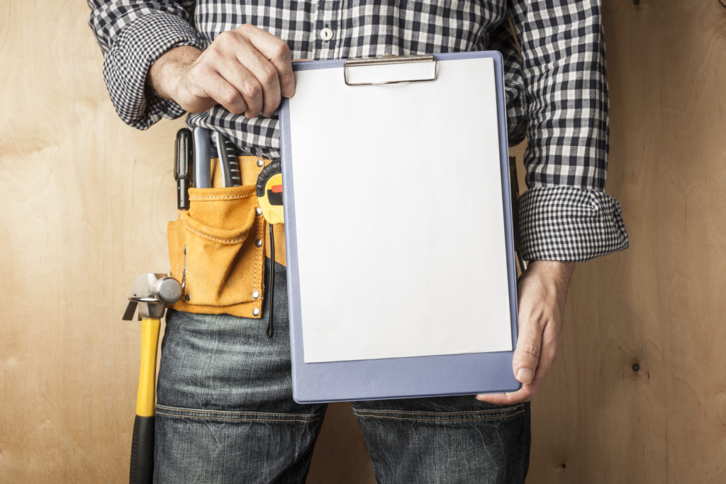 a contractor stands with a clipboard list of construction business clients