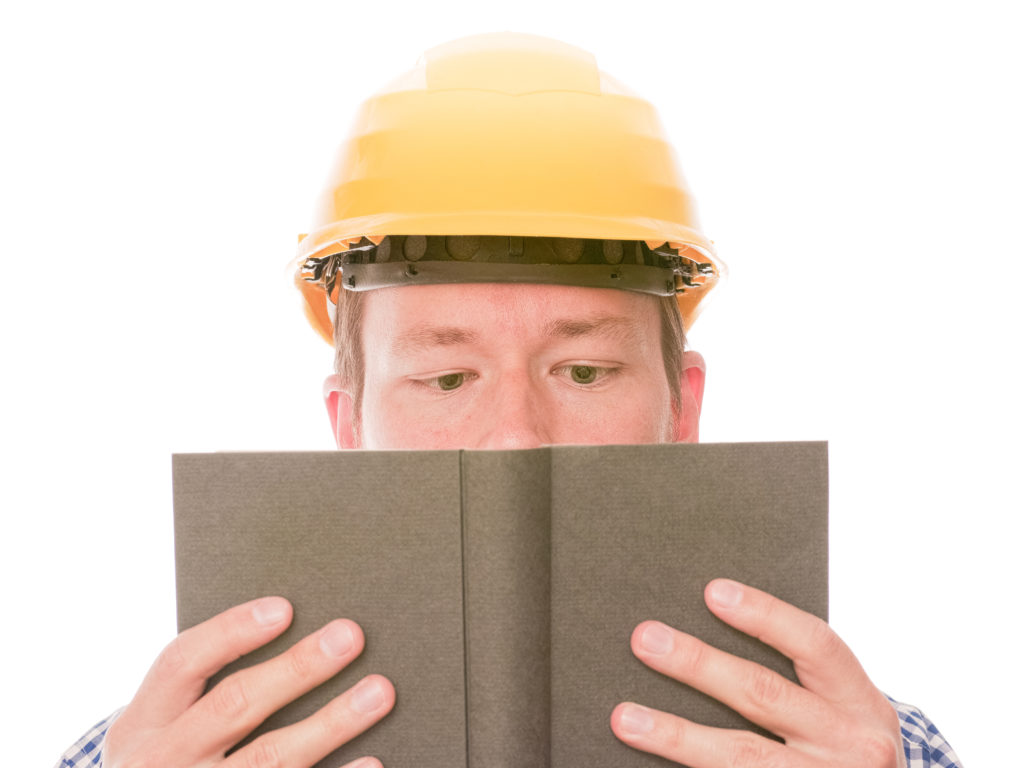 a contractor in a yellow hard hat holds a book in front of his face