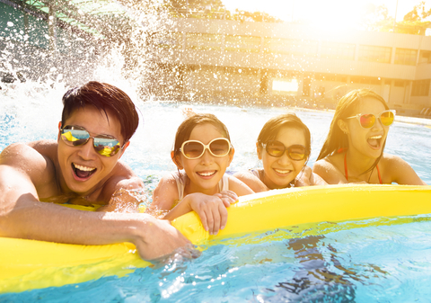 A family of four wearing sunglasses holds onto a yellow pool float while splashing in a pool in the sun.